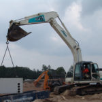 Large Backhoe lifting and setting concrete block