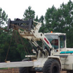 Backhoe forklife carrying large concrete block on chains