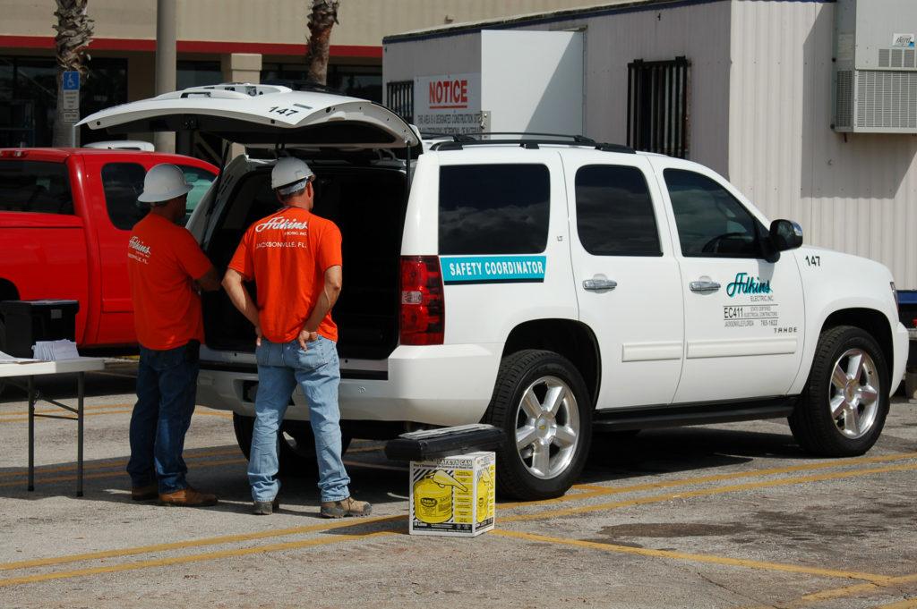 Employees in hardhats looking inside Adkins Safety Truck